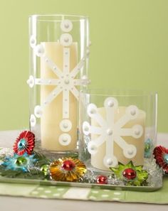 Create a modern Christmas feel by using white tape, stickers and other craft store supplies to create snowflakes designs on clear hurricane candle holders. More Christmas centerpieces: http://www.midwestliving.com/homes/seasonal-decorating/easy-christmas-centerpiece-ideas/?page=11http://www.midwestliving.com/homes/seasonal-decorating/easy-christmas-centerpiece-ideas/?page=11