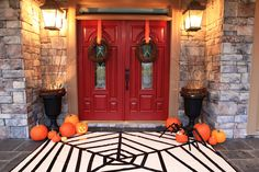 Halloween front porch from #BowerPowerBlog!  Loving everything from the uplights in the planters and simple ribbon on grapevine wreaths to the awesomely graphic DIY spiderweb rug (drop cloth and black tape) and pumpkin spider (legs are sprinkler tubing).