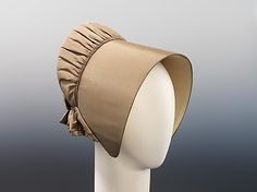 """Silk Quaker bonnet, American, ca. 1850. Shows the simplicity of form and exquisite workmanship that Quaker hats were renowned for. Instead of the deep pleats often used by Quakers, this model is gathered where the crown meets the brim, giving the illusion of being pleated. """"Belonged to Mrs. John J. Merritt, great grandmother of Winthrop Trowbridge who lived at 114-116 Columbia Heights from 1827-1871""""."""