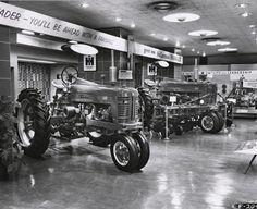 A Farmall 300 and 400 tractor on display in a showroom. The showroom may have been at the International Harvester headquarters in Chicago, Illinois. Antique Trucks, Antique Tractors, Vintage Tractors, Vintage Farm, Farmall Tractors, Old Tractors, John Deere Tractors, Old Ford Trucks, Lifted Chevy Trucks