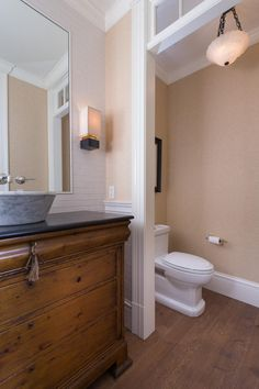 This formal powder room features a mix of neutral colors and textures that add a twist to traditional style. Natural wood flooring, Calcutta marble vessel sink and two different wall textures are all included to make this space more streamlined and contemporary.