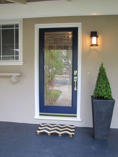 "Redone Home Exterior - House Paint - Body: Wise Owl + 200% by Kelly Moore Door color: ""Naval"" by Sherwin Williams Porch light - Quentin Pendant Sconce by Restoration Hardware.  Chevron Door Mat by Ballard Designs Concrete Floor stained to a Charcoal Gray"