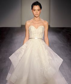 Ivory silk organza floral embroidered bridal ball gown, strapless sweetheart neckline, satin ribbon at natural waist, tiered tulle and organza skirt trimmed with horsehair, chapel train. Available in Ivory.