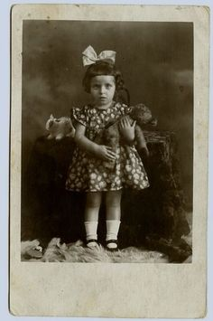 REAL PHOTO POSTCARD LITTLE GIRL WITH A BOW IN HER HAIR HOLDS TEDDY BEAR RPPC