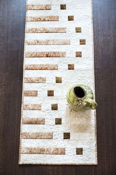 Shannon Schlosser's table runner gives the illusion of a wave pattern by varying lengths of squares and rectangles. We love the rich neutral palette and easy construction. Bravo!