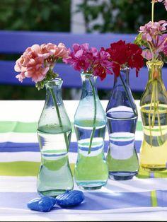 Bunte FlaschenGeranienBunte Flaschen als Vasen für Einzelblüten benutzen und in einer Reihe aufstellen.