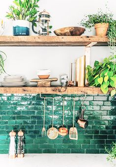 Green tile, open shelves, brass utensils.