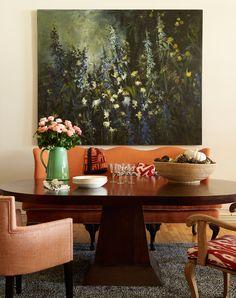 The dining room of a SoHo loft, featuring a John Alexander landscape above a camelback sofa. Courtesy of The Monacelli Press | Lonny November 2014