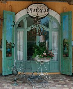 Antique Store with Turquoise Doors and French Style Windows with a Chandelier and Bistro Table