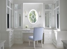 Bryant Sconce walk-in oval window built-ins built-in cabinets white vanity cabinets marble countertops sconces flanking window mirrored doors mirrored cabinets powder blue chair powder blue vanity chair