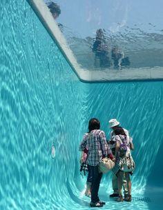 leandro elrich pool instalación que creó en 2011 en el Museo de Arte del Siglo XXI en Kanawaza (Japón), simulando el interior de una piscina.  Los visitantes podían entrar en la piscina y observar hacia arriba sin mojarse, proporcionando una sensación auténtica de estar debajo del agua. Elrich lo consiguió a través de un espacio vacío rodeado por paredes de color aguamarina