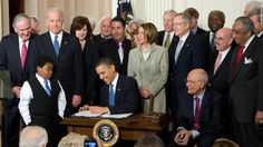 US President Barack Obama, surrounded by lawmakers, signs the healthcare insurance reform legislation during a ceremony in the East Room of the White House in Washington, DC, March 23, 2010. Obama Tuesday signed into law sweeping reforms that will for the first time ensure health care coverage for almost every American. AFP PHOTO / Saul LOEB (Photo credit should read SAUL LOEB/AFP/Getty Images)