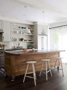 banquetas e ilha de madeira em cozinha