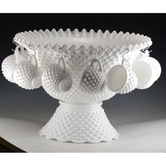 Sold: $325   Punch bowl set in Hobnail Milk Glass by Fenton.  This pre-logo set was produced  in 1958 to 1967.  It was reissued later, but those pieces would have the embossed logo. Issued as Ware number 3712, as a 15 piece set which included a plastic ladle.  The bowl measures 15 inches across and is 7 1/2 inches high.  The base is 8 1/4 inches across and 4 inches high.  It comes with 12 punch cups which are 3 inches across and 2 1/2 inches tall.