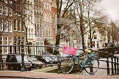 Bright bicycle in Amsterdam. Beautiful building behind and famous canal of the city.