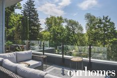 A grey gray outdoor sectional makes this deck an oasis! And the glass railing gives a view of all the surrounding trees.