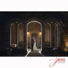 Night time photograph taken in the carriage ring at Fawsley Hall. Stunning stonework frames this wedding image.