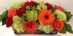 This pave style design would look stunning as a dining room centerpiece or on a low cocktail table. we can see it in your entryway or kitchen island as well! Showcasing deep red and fiery orange roses, lime hydrangea and ornamental kale for a chic garden arrangement.