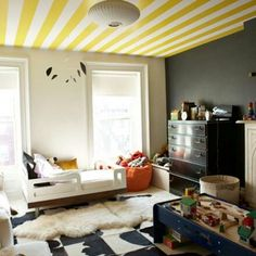 Yellow white stripe ceiling, black wall and furniture, cowhide and sheepskin rugs, splash of orange