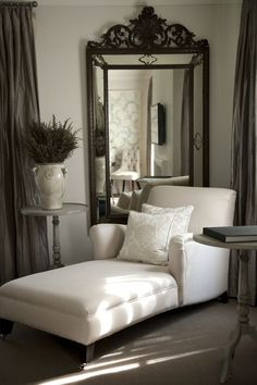 How lovely.  Great use of a large mirror in a low ceiling.  The way the dark draperies tie to the mirror frame with the paler grays is really nice.....John Jacobs interior