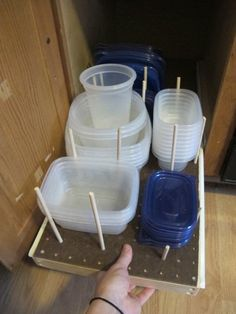 Doesn't it seem like every time you go to grab a plastic container for your leftovers, the lid is missing? Use a sliding drawer and wooden pegs to keep all of your items in an orderly cabinet. Click through for more on this and other kitchen organization ideas.
