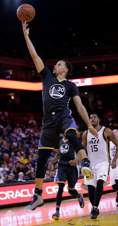 Description of . Golden State Warriors' Stephen Curry drives to the basket pass Utah Jazz's Derrick Favors (15) during the second half of an NBA basketball game Saturday, March 21, 2015, in Oakland, Calif. Golden State won 106-91. (AP Photo/Marcio Jose Sanchez)