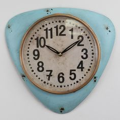 What an unusual find! This distressed wall clock features a powder blue, distressed finish. In the shape of a triangle, complete with a circular clock face protected by transparent acrylic. The large bold numerals are very easy to read, amongst a subtle aged background, ideal for a work shop, garage or shed! The retro blue clock will add a touch of art deco style to any room. Easily mounted to the wall by using the hook to the back. Requires one AA battery (not included)
