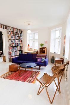 Floor to ceiling bookshelves. Modern blue sofa. Butterfly chair. Boho rug