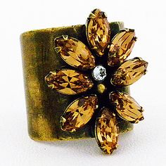 Sorrelli Riverstone Collection, Fashion Rings. Golden Shadow crystals create a desert flower on an antique gold cigar band. Fun fashion for your digits.