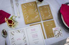 Hochzeitstisch mit weiß bedruckten Einladungskarten auf Goldpapier.
