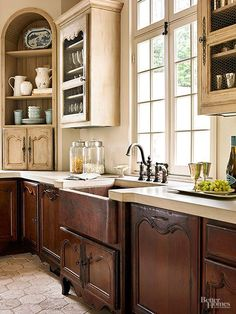 Gorgeous copper sink in a french kitchen design.  Love the two toned cabinets.