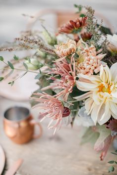 Late autumn centerpiece with antique mums and dahlias in muted tones of copper…