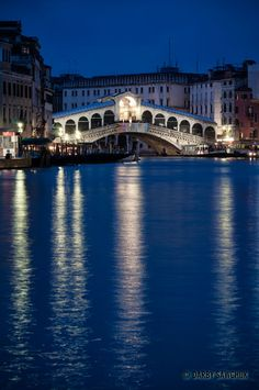The Rialto Bridge spanning the Grand Canal lit up at dusk in Venice