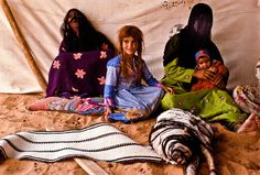 Shammar ladies with children in encampment in the Nafud Desert. Handwoven goat's hair tent strap in the foreground.