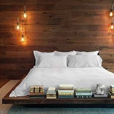 all white bedding on a low bed against a wood paneled wall and ceiling mounted industrial lighting pendants