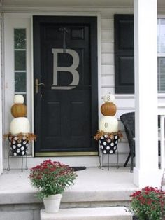 Pumpkins stacked on hand painted terra cotta pots with a leafy garland accent.