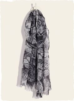 Shadowy batik lotus blossoms pattern the gauzy wool scarf in shades of grey and charcoal, with frayed ends.