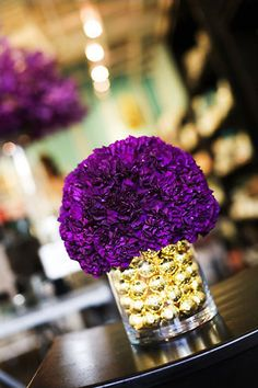 purple carnation (yes I know, dreaded by some brides but gorgeous in deep purple and clean and contemporary too!) in a vase filled with gold; we could use silver instead.