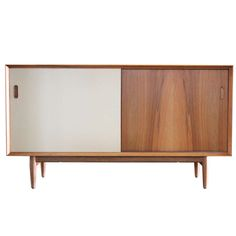 A bleached walnut cabinet with reversible sliding doors (walnut on one side and off-white lacquer on the other) Designed by Arne Vodder for Sibast ca.1950's