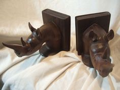 """BIG!! 100% SOLID WOOD CARVED RHINOCEROS  BOOK ENDS! Not perfect. One of the bookends has part of the tip of the horn that chipped off  (as in photo) and on the same book end there is a small chip on the edge of the book connected to the rhino head (also pictured) but they still look amazing! 5"""" tall and 8"""" wide   BIN $129.99 plus $14.52 shipping --very nice!--  **want**"""