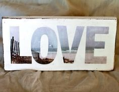 Oooh I love this!  Letters cut out of single photograph and placed on painted wood.  You could also transfer the photo to the wood, cut out letters from contact paper, paint over them and viola!