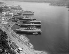 View of the Puget Sound Naval Shipyard at Bremerton, Washington (USA), in August 1992. The following ships are identifiable (front to back): Three Agile-class minesweepers, with USS Pluck (MSO-464) as the first in the row; USS Hornet (CVS-12); USS New Jersey (BB-62); USS Roark (FF-1053); USS Stein (FF-1065); USS Oriskany (CV-34) with a Knox-class frigate; two Asheville-class gunboats; USS Bennington (CVS-20) with an old WWII-submarine alongside; USS Midway (CV-41) with six Knox-class…