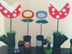 Super Mario Bros. Party decorations. Piraña plant, fire power and ice power flowers made from PVC pipe from Home Depot, green spray paint, wooden dowels, hot glue and card stock. I used a free printable for the images on the front.