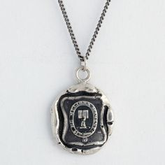 This handcrafted talisman necklace reads, in Latin, Better Fortunes Await Me. The hand holding an open book symbolizes the manifestation of hopes and dreams.  $150.  Each Pyrrha talisman is cast in reclaimed sterling silver or bronze from a 19th century wax seal and is handcrafted in Vancouver, Canada.
