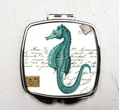 """Turquoise Seahorse Pocket Mirror Mermaid Compact Mirror. Turquoise Seahorse Pocket Mirror. Hand printed in my Bungalow Blue Studio, this stainless steel Square compact mirror features a high shine. Measures 2.25"""" by 2.25"""" My printing process produces an image that is permanently infused into metal. The process creates a waterproof image that is scratch resistant. Your image will not smudge, crack, fade or peel."""