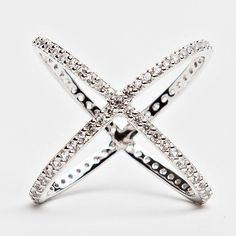 Style #100 Sterling Silver Rhodium White-Gold, with Created White Sapphire Description Criss crossing bands of precious metal are decorated with brilliant pavé-set crystals on this slender and versati