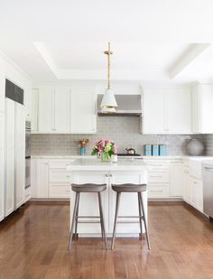 White and gray kitchen boasts white shaker cabinets paired with white marble countertops and a gray subway tile backsplash accented with white grout.