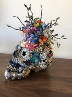 Life size skull encrusted with vintage jewels, topped with a ceramic antique capodimonte bouquet.