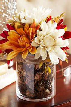 arrangement of faux dahlias, complete with a glass vase filled with pinecones