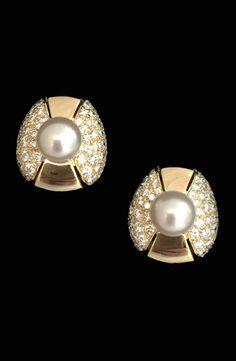 Une paire de boucles d'oreilles en or jaune 750/000 signée de la Maison Cartier centrée d'une perle de culture blanche épaulé de deux motifs pavés de diamants taille brillant.   Diamètre perle : 0,7 cm environ.   Poids total des diamants : 2,20 carats environ.   Longueur : 1,8 cm.   Largeur : 1,5 cm.   Poids brut : 14,1 grammes.